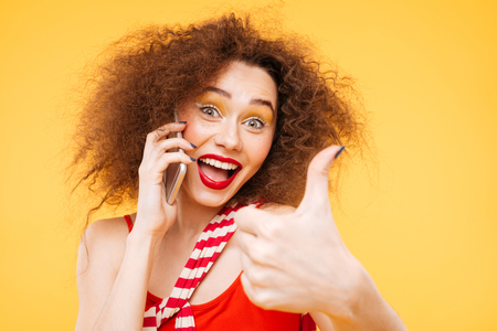 Funny Bright model talking at phone and showing thumb up. Isolated orange background