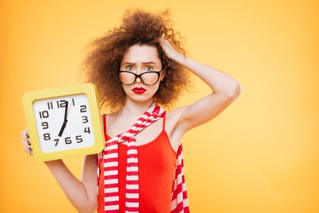 Not understand Bright model in glasses holding clock in hand, touching hair and looking at camera. Isolated orange background