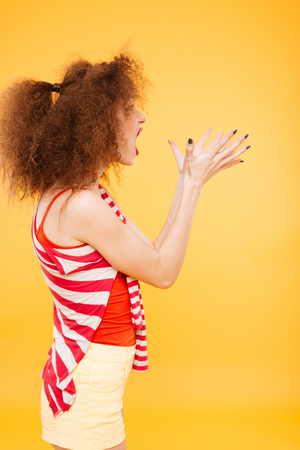 Vertical image of Surprised Bright model in studio. Woman showing surprised gesture. Side view. Isolated orange background