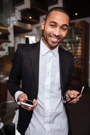 looking away from camera: Vertical image of smiling african man in suit holding phone and eyeglases in hotel