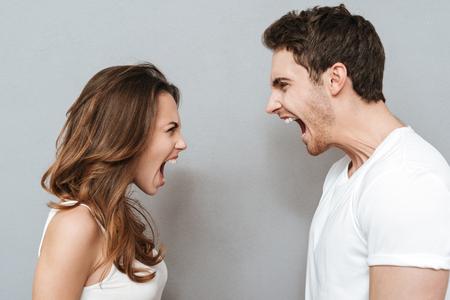 Couple qui crie en regardant les uns les autres. Fond gris isolé