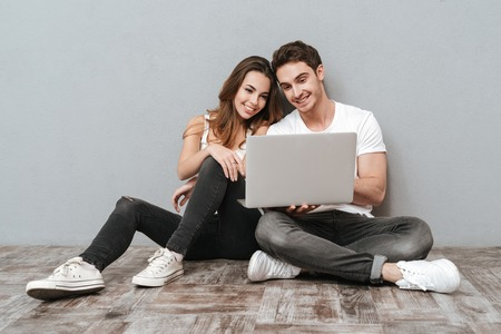 Couple sitting on the floor with laptop computer in studio. Full length image. Isolated gray background Stock Photo