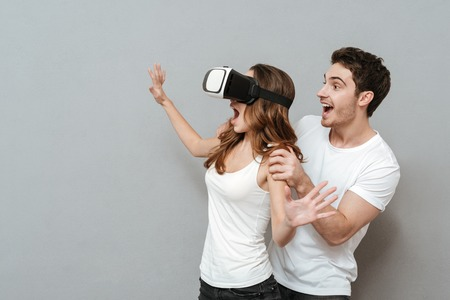 Couple with virtual reality device in studio. Woman using device and man standing from the her back. Isolated gray background Stock Photo