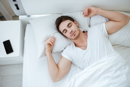Top view of handsome young man in white t-shirt sleeping in bed Banco de Imagens