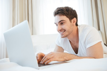 Happy man using laptop and lying on bed. Side view
