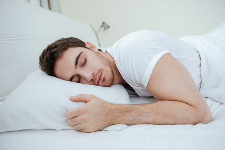 ベッドの枕の上で眠っているハンサムな若い男