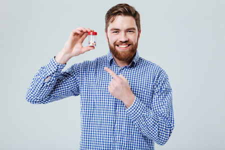 Happy bearded young man holding and pointing on bottle of pills over white background Stock Photo