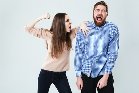 Angry furious young woman arguing with her husband over white background