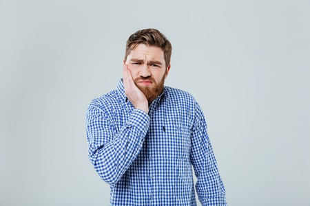 Sad bearded young man standing and having toothache over white background Stock Photo