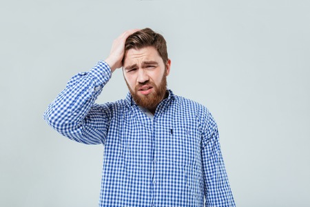 Depressed bearded young man standing and having headache over white background