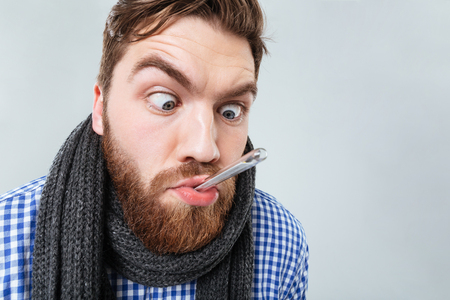 Funny bearded young man in scarf with thermometer in his mouth over white background 版權商用圖片 - 75256779
