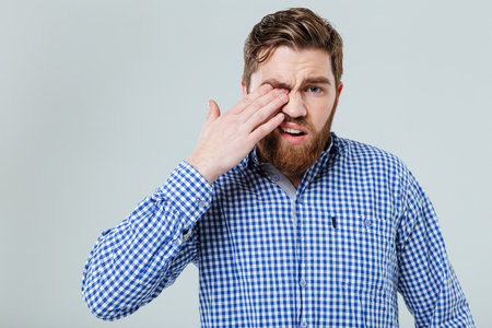 overtired: Upset bearded young man standing and rubbing his eye over white background Stock Photo