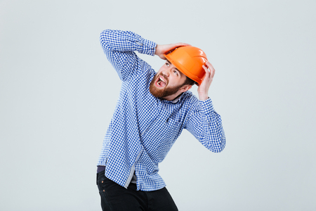 Shocked bearded young man in helmet covered his head by hands and screaming over white background
