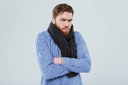 Sad ill bearded man in scarf with thermometer in his mouth over white background