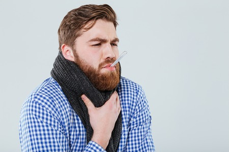 Sick bearded young man in scarf holding thermometer in his mouth measuring temperature over white background Stock Photo