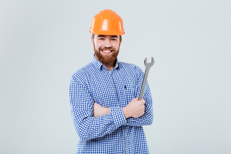 Happy bearded young man in orange helmet standing and holding wrench over white background