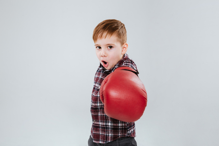 litle: Litle boy in boxing gloves standing and fighting over white background Stock Photo