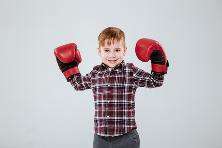Happy cute little boy in red boxing gloves standing with raised hands over white background Stock Photo