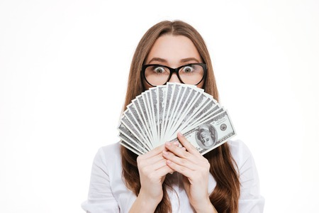 Happy young woman in formalwear holding paper currency in her hands and looking out of them while standing isolated on white