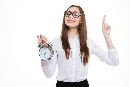 Charming young businesswoman in eyeglasses holding alarm clock and pointing finger isolated on a white background Stock Photo