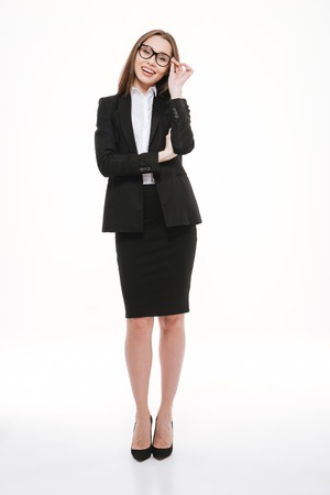 Full length portrait of smiling young business woman in jacket standing over white background