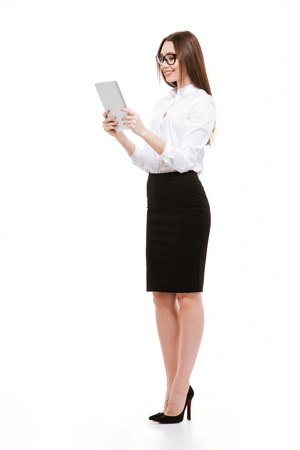 Side view portrait of a beautiful smiling businesswoman using tablet computer isolated on a white background