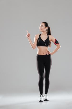指差しながらイヤホンで音楽を聴くに灰色の背景上に立っている幸せな若いフィットネス女性の写真。