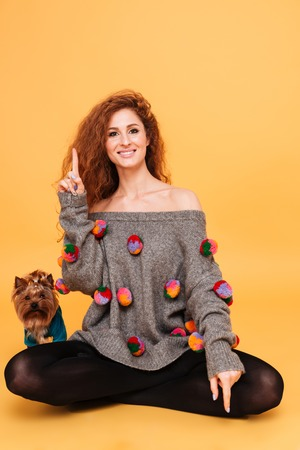Portrait of a happy pretty woman sitting with her little dog yorkshire terrier and pointing finger up isolated on orange background
