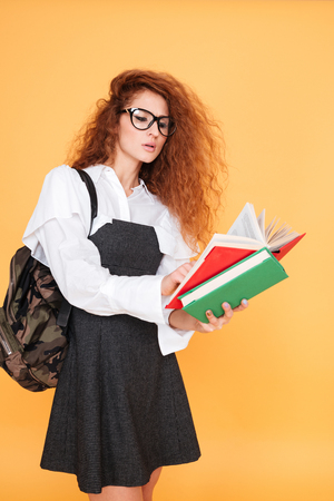 glases: Concentrated young woman in glases with backpack standing and reading book