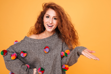 looking away from camera: Positive attractive woman with long red hair pointing away isolated over orange background