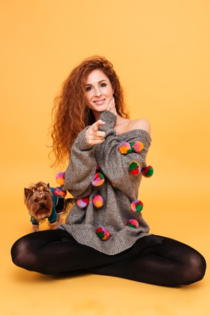 Portrait of a smiling young woman sitting with her little dog yorkshire terrier and pointing finger at camera isolated on orange background