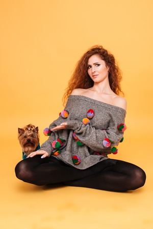 Portrait of a young pretty woman sitting and pointing at her little dog yorkshire terrier isolated on orange background