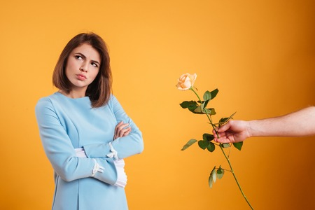 Sad frowning young woman receiving rose and standing with arms crossed over yellow background Imagens