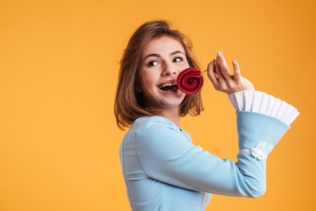 Happy beautiful young woman smiling and eating lollipop over yellow background Stock Photo