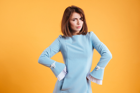 Frowning serious young woman standing with hands on waist over yellow background Stock Photo