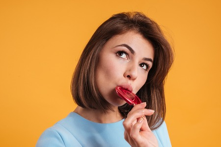 Thoughtful attractive young woman thinking and eating lollipop over yellow background