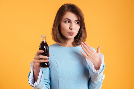 Pensive cute young woman drinking soda from the bottle over yellow background