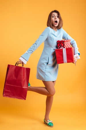 Full length of amazed young woman running with present boxes and shopping bag over yellow background