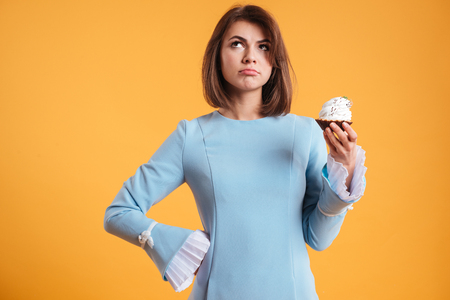 Thoughtful young woman holding cupcake and thinking over yellow background Stock Photo