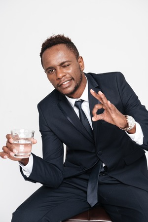 Image of young businessman drinking water while sitting. Isolated over white background. Look aside.