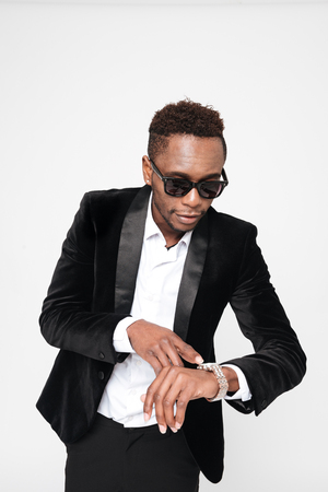 Photo of young african businessman wearing glasses looking at watch. Isolated over white background.