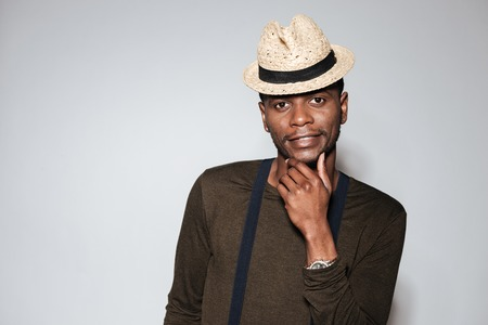Photo of handsome young african man wearing hat standing in studio. Isolated over grey background.