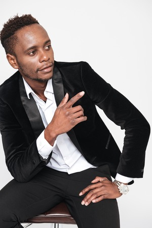 Picture of attractive young african businessman sitting on stool while pointing. Isolated over white background. Look aside.