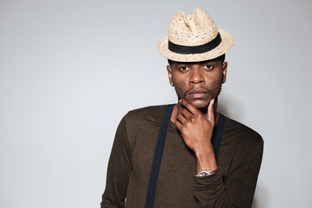 Image of attractive young african man wearing hat standing in studio. Isolated over grey background.