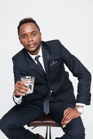 Photo of african businessman drinking water while sitting. Isolated over white background. Look at camera.