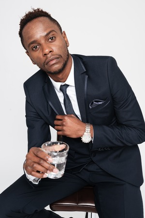 Image of african young businessman drinking water while sitting. Isolated over white background. Look at camera.