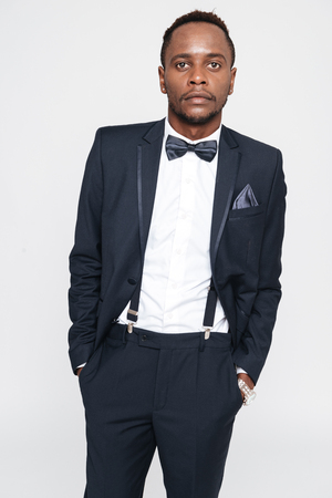 Image of young handsome african businessman posing in studio. Isolated over white background. Look at camera.