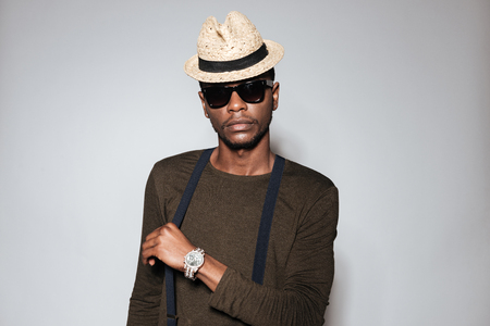 Image of young african man wearing hat and glasses standing in studio. Isolated over grey background. Stock Photo