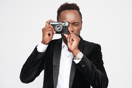 Photo of handsome young african businessman make a photo by his camera. Isolated over white background.
