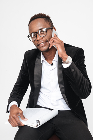 Image of attractive young african businessman talking by phone while holding book. Isolated over white background. Look at camera.